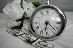 Black and white photo of pocket watch, three white roses, three photobooth pictures of a couple on a white tablecloth